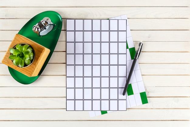 Maquete de espaço de trabalho de escritório em casa com caderno, caneta, despertador, planta em vaso na mesa de madeira