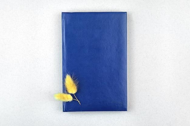 Maquete de espaço de trabalho mínimo com bloco de notas de couro azul e flores secas secas, foto de vista superior da área de trabalho do escritório