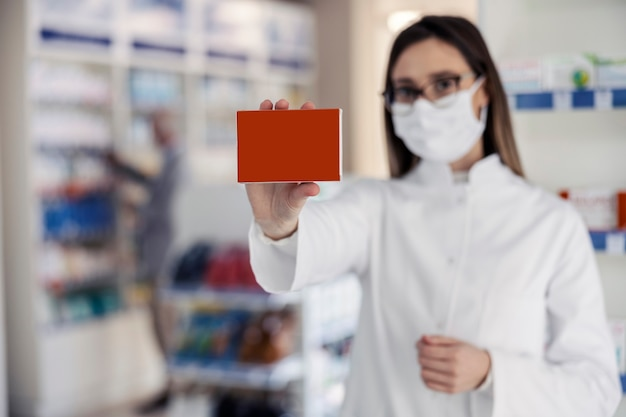 Maquete de farmácia para embalagem de produtos com placa vermelha. a mão de uma mulher segura uma caixa de remédios, o foco está na caixa enquanto o retrato da mulher copia espaço para anúncios