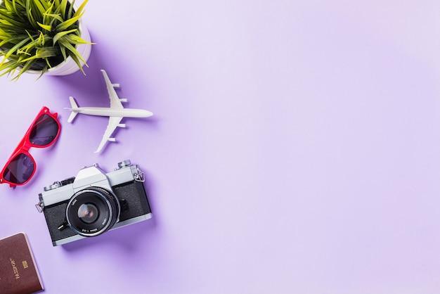 Maquete de filmes de câmera retro, avião, óculos de sol, acessórios para viajantes