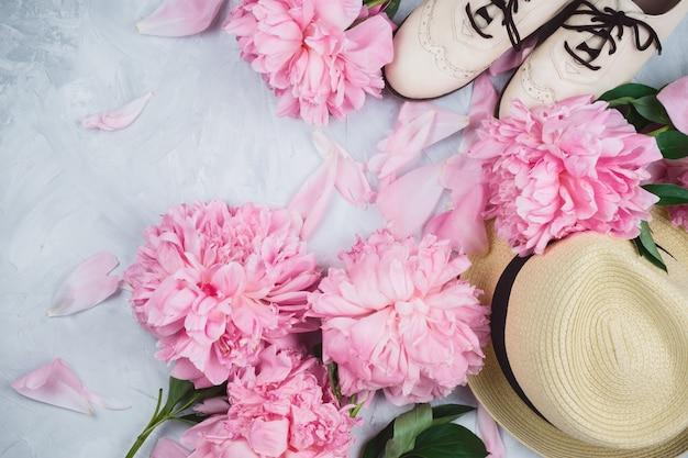 Maquete de flatlay feminina com chapéu, peônias rosa e sapatos de sotaque branco em cimento