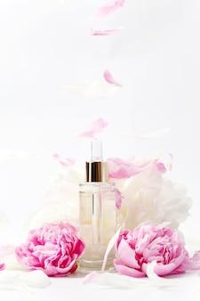 Maquete de frasco de vidro transparente com conta-gotas com soro cosmético, óleo, essência entre flores de peônia rosa e branca na superfície branca, presente de dia dos namorados