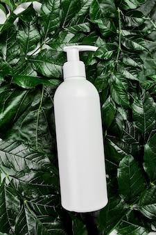 Maquete de garrafa branca em branco nas folhas tropicais verdes, conceito de spa, plástico de embalagem de cosmético orgânico natural, vista superior do tubo de creme, anúncio de composição plana leiga ou modelo de banner