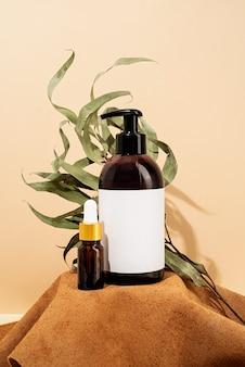 Maquete de garrafas marrons para acessórios de spa de cosméticos naturais em fundo de creme e pódio de couro marrom