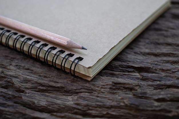 Maquete de lápis e livro na velha mesa de madeira, close-up
