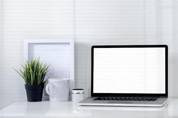 Maquete de laptop com tela em branco na mesa superior branca em um escritório moderno com sombra na parede