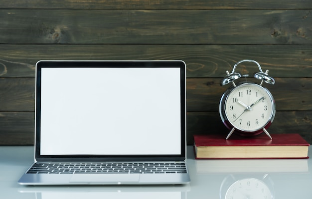 Maquete de laptop e despertador com fundo de madeira em cima da mesa de trabalho