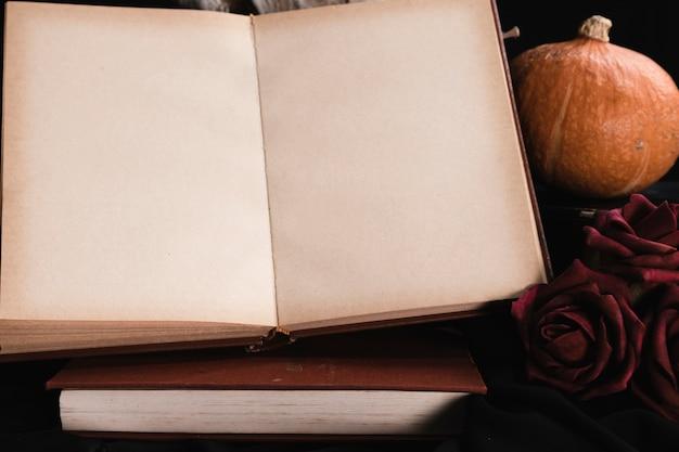 Maquete de livro aberto com rosas e abóbora