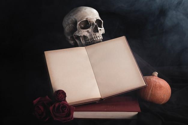 Maquete de livro aberto com rosas e caveira