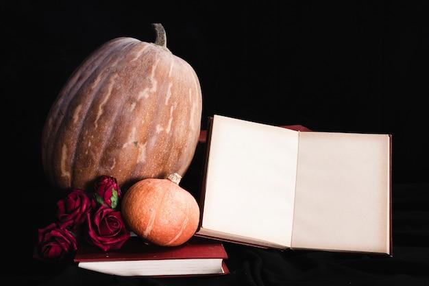 Maquete de livro com abóboras e rosas