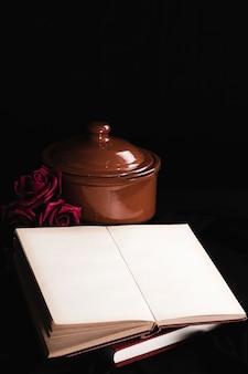 Maquete de livro com rosas e pote marrom