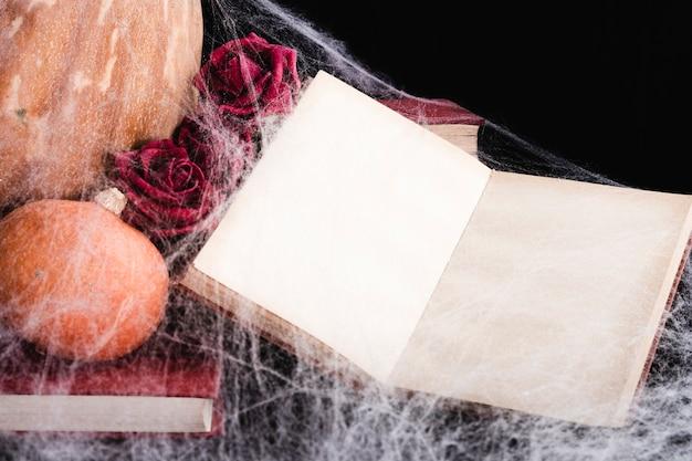 Maquete de livro com teia de aranha e abóboras