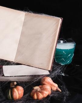 Maquete de livro com teia de aranha e bebida