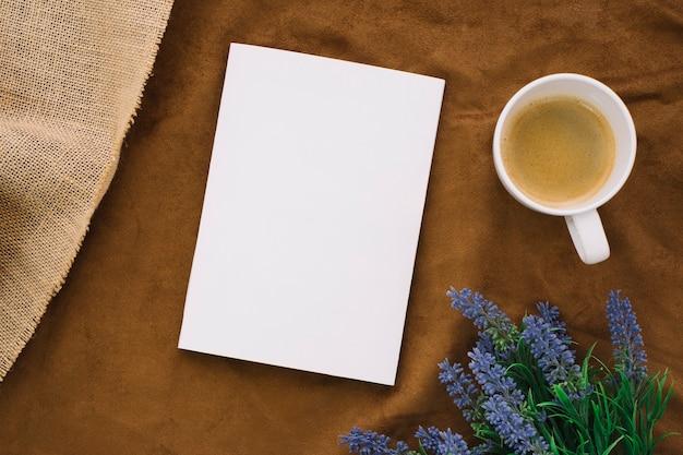 Maquete de livro em branco com café e flores