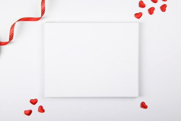 Maquete de lona com corações vermelhos e fita de decoração festiva em um fundo branco. elemento de design para parabéns dia dos namorados e dia das mães