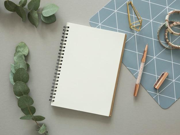 Maquete de mesa de trabalhos da mulher mínima. caderno espiral aberto com espaço de cópia, papelaria ouro e ramo de eucalipto. postura plana