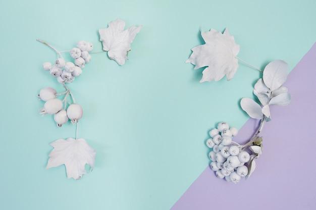 Maquete de moldura branca com abóbora, frutas e folhas em fundo de outono de papel turquesa e violeta.