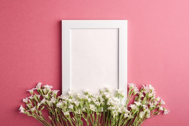 Maquete de moldura branca vazia com flores de morrião dos passarinhos orelha de rato