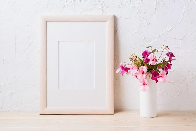 Maquete de moldura de madeira com buquê de flores rosa e roxo