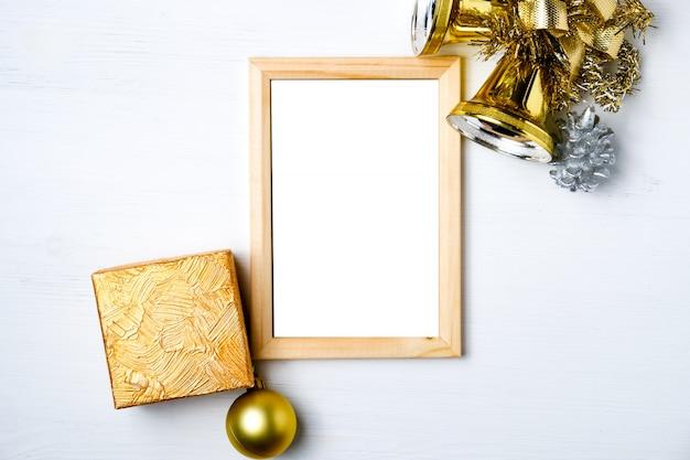 Maquete de moldura de madeira com decorações de ano novo, sinos e presentes