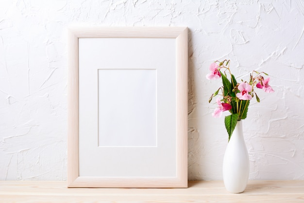 Maquete de moldura de madeira com flores silvestres roxas em vaso elegante