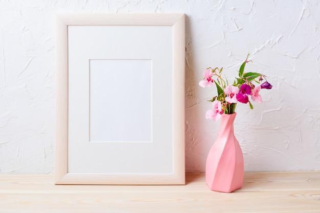 Maquete de moldura de madeira com flores silvestres roxas em vaso rosa