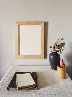 Maquete de moldura de madeira. design minimalista escandinavo. vaso de flores em uma pilha de livros sobre uma velha mesa de madeira. composição em uma superfície de parede branca