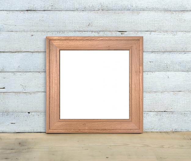 Maquete de moldura de madeira quadrada fica em uma mesa de madeira