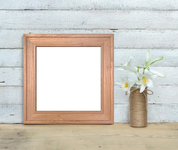 Maquete de moldura de madeira quadrada perto de um buquê de lírios fica em uma mesa de madeira