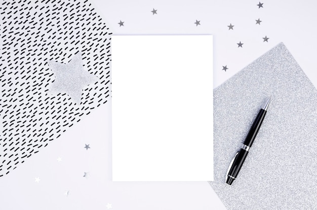 Maquete de moldura de prata de vista superior cartão de papel em branco e caneta preta com arranjo de decorações de natal.