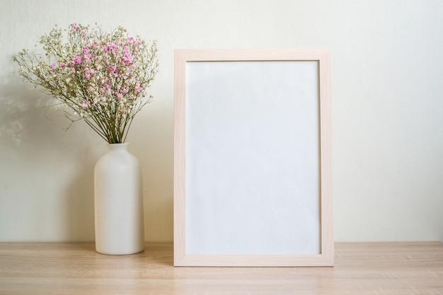 Maquete de moldura de retrato branco retrato na mesa de madeira. vaso de cerâmica moderno com gipsófila.