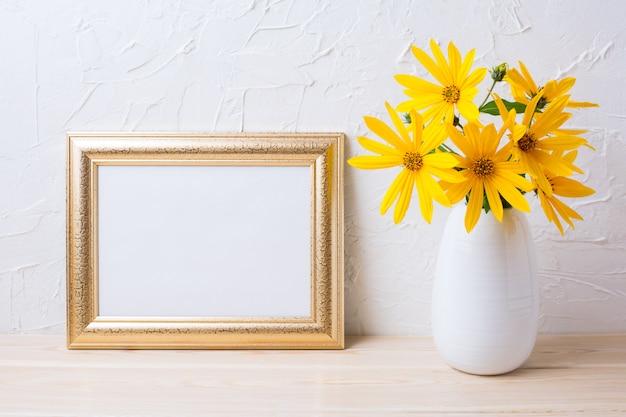 Maquete de moldura dourada paisagem com flores de rosinweed amarelo