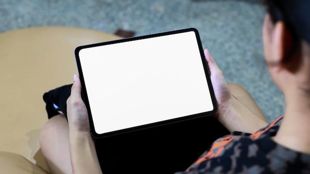 Maquete de mulher segurando uma tela de tablet branca em casa. idéia criativa
