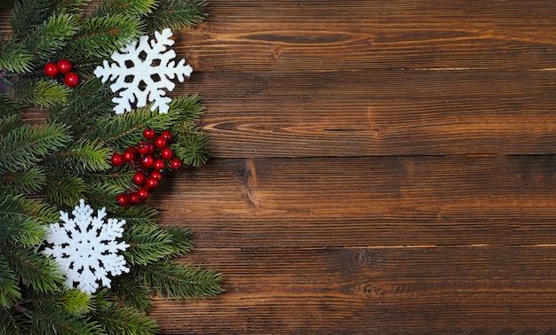 Maquete de natal e ano novo com galhos de pinheiros e enfeites vermelhos e dourados no fundo de madeira.