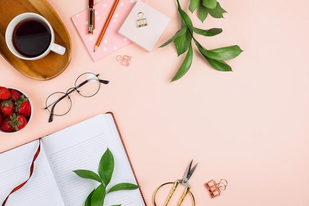 Maquete de negócios flatlay com xícara de café em uma bandeja de madeira, morangos em uma tigela, caderno aberto, óculos, ramos de ruscus e outros acessórios em fundo pastel com copyspace