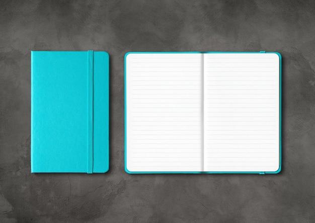 Maquete de notebooks forrados fechados e abertos azul-marinho isolado em concreto escuro