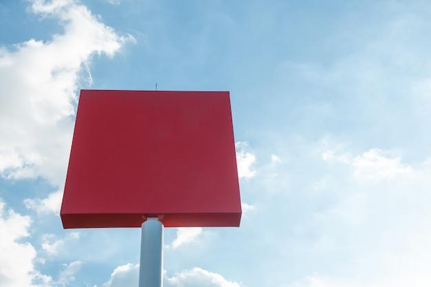 Maquete de outdoor em branco com tela vermelha contra nuvens e fundo de céu azul