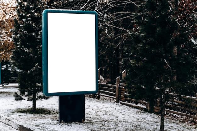 Maquete de outdoor em branco para publicidade, na estrada de inverno nas montanhas. outdoor em branco pronto para novo anúncio na floresta