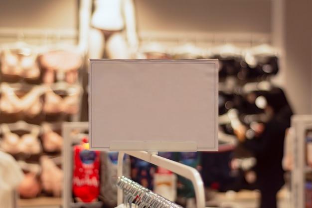 Maquete de papel branco de uma tabuleta de desconto no fundo de uma loja com roupas.