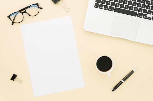 Maquete de papel plana plana ao lado do laptop