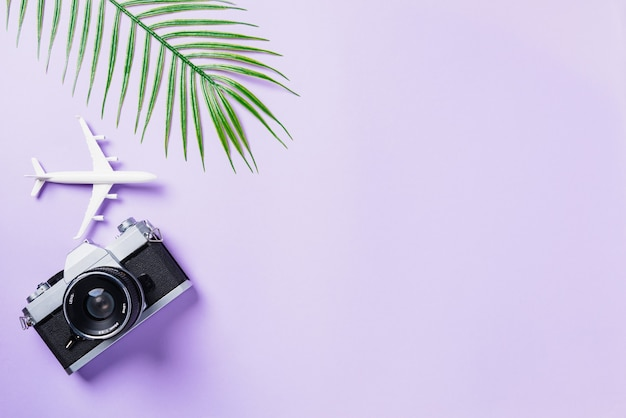 Maquete de plano plano de vista superior de filmes de câmera retro, folhas de avião e acessórios para viajantes