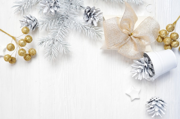 Maquete de presente de natal arco de ouro e cone de árvore, flatlay em um branco