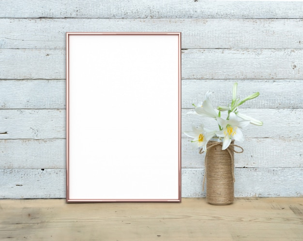 Maquete de quadro a4 vertical ouro rosa perto de um buquê de lírios fica em uma mesa de madeira sobre um fundo branco de madeira pintado. estilo rústico, beleza simples. 3 render.