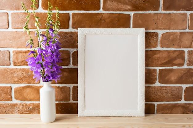 Maquete de quadro branco com buquê de campânula perto da parede de tijolos expostos