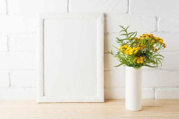 Maquete de quadro branco com flores amarelas perto de paredes de tijolos pintados