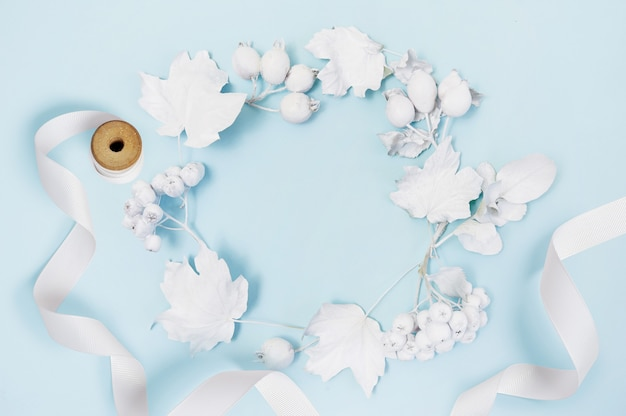 Maquete de quadro com abóbora branca, fita, bagas e folhas