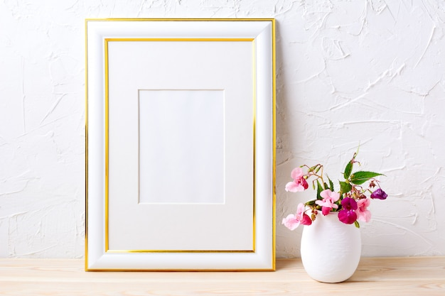 Maquete de quadro decorado ouro com buquê de flores em vaso