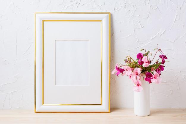 Maquete de quadro decorado ouro com buquê de flores rosa e roxo