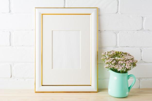 Maquete de quadro decorado ouro com tijolos e flores cor de rosa suaves