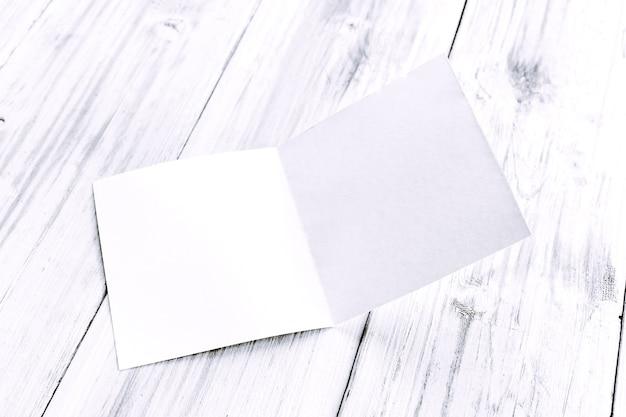 Maquete de revista de papel em branco branco na mesa de madeira